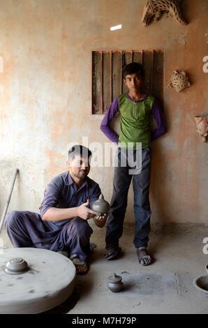 Indian man potter showing a clay bowl thrown on a hand made potters wheel Bishnoi Village Jodhpur Rajashan India - Stock Photo