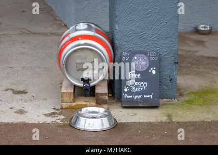 A beer keg barrel converted to pour water into a dog drinking bowl outside a pub with the words 'Free Doggy Beer! - Stock Photo