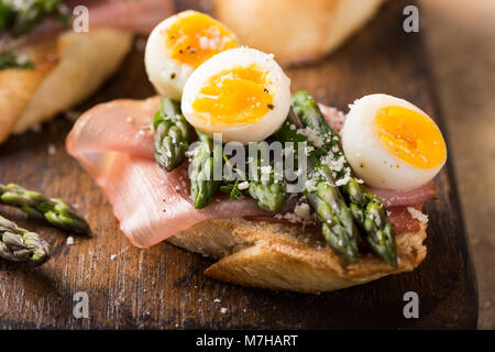 Fresh sendwich with ham, asparagus and quail eggs - Stock Photo