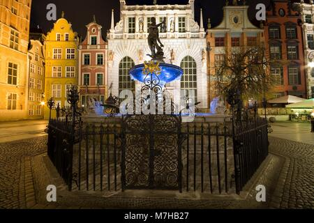 Illuminated Neptune Fountain and Artus Court at Long Market (part of Royal Route) in Gdansk at night, Poland - Stock Photo