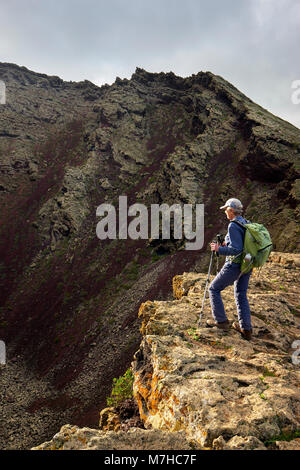 Walker standing on the caldera rim of Montana Corona, near Ye, Lanzarote, Canary Islands, Spain - Stock Photo