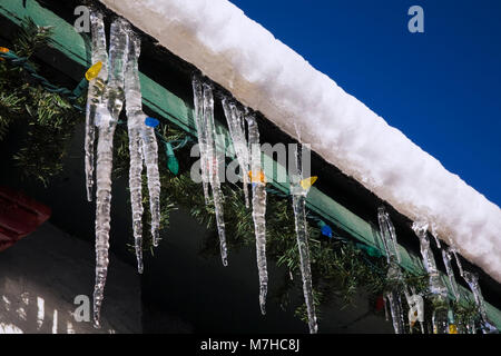 Snow and ice with Christmas lights and icicles hanging from the eaves on a building in winter. - Stock Photo