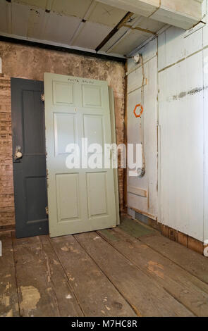 Stacked wooden doors and partially demolished plaster and wooden wall in a empty room inside an old 1800s cottage - Stock Photo