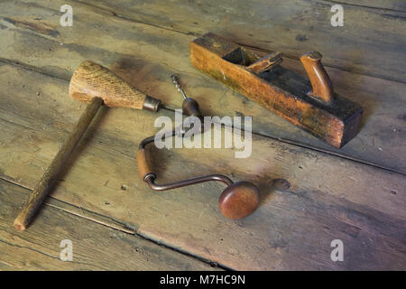 Old mallet, manual hand drill and hand plane on wooden floor in empty room inside an old 1800s cottage style home. - Stock Photo