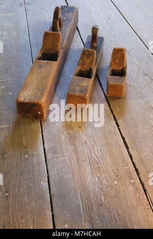 Old wooden hand planes on wooden floor in empty room inside an old 1800s cottage style home. - Stock Photo