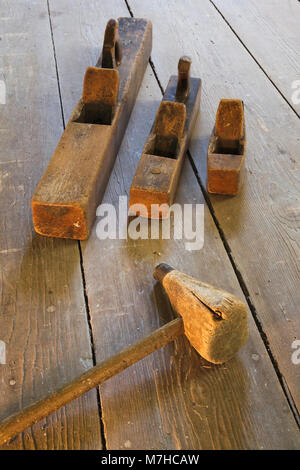 Old wooden mallet and hand planes on wooden floor in empty room inside an old 1800s cottage style home. - Stock Photo