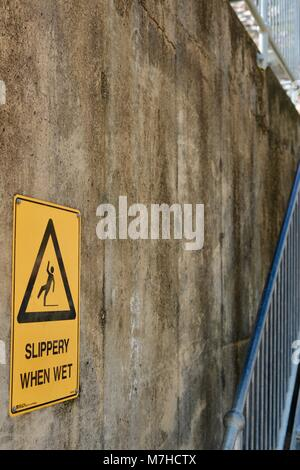 slippery when wet sign with image of man falling over, Ross River Dam, Ross Dam Access, Kelso QLD, Australia - Stock Photo