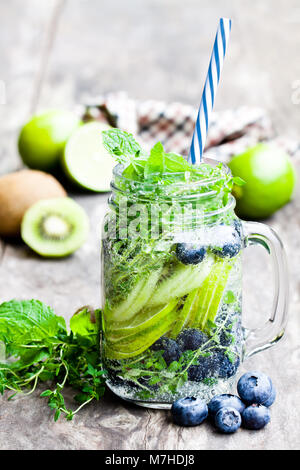 Detox  water. Homemade summer fruit drink with lime and kiwi and blueberry - Stock Photo