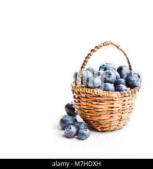 blueberries  in wicker basket isolated on white background - Stock Photo