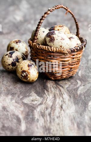 Quail  eggs in a small wicker basket - Stock Photo