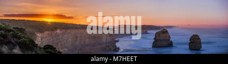 The nearly full moon rising over the sea cliffs near Port Campbell, Australia. - Stock Photo