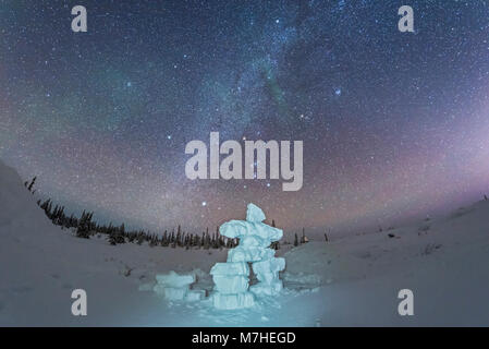 Milky Way and winter stars over a mock-up inukshuk figure made of snow, Canada. - Stock Photo