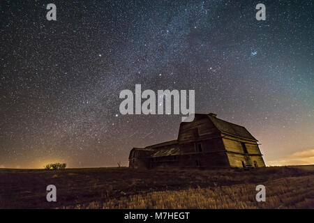 Orion and the winter Milky Way over an old barn in Alberta, Canada. - Stock Photo