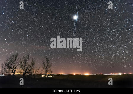 A pair of nearly simultaneous and parallel Iridium satellite flares descend into the north. - Stock Photo