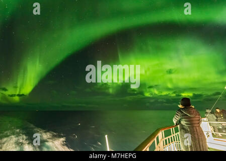 Watching the northern lights from the aft deck on a cruise ship on the coast of Norway. - Stock Photo