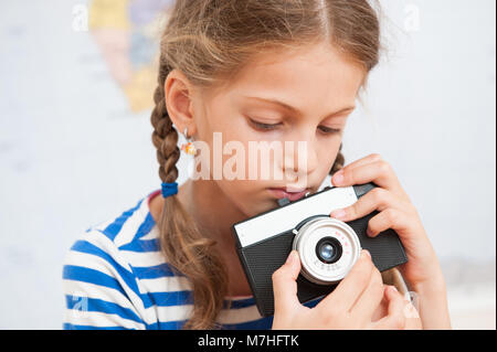 portrait of cute little girl holding a vintage film camera - Stock Photo