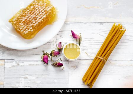 organic honeycomb, honey lip balm and natural wax candles on wooden white background - Stock Photo