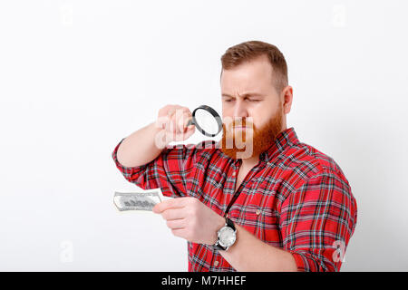 man looking at magnifying glass for bill - Stock Photo