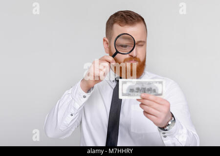 expert looking at magnifying glass for bill - Stock Photo