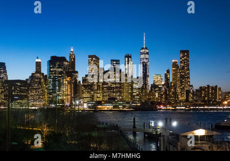 The Lower Manhattan skyline as seen from Dumbo, Brooklyn at night - Stock Photo
