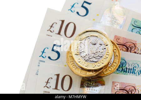 Pile of new 12-sided English one pound coins £ pounds sterling money cash on new polymer plastic £10 and £5 notes - Stock Photo