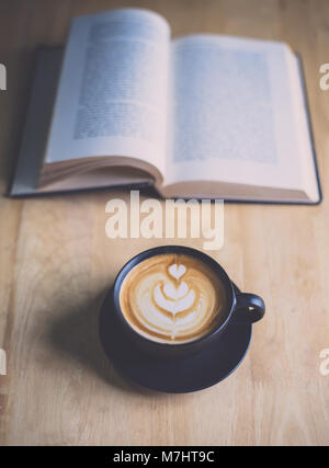 Latte art coffee in black cup with open book on wood table in coffee shop - Stock Photo