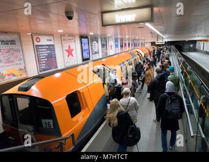 View of subway train and passengers at subway station platform on the Glasgow Subway system , Scotland, United Kingdom - Stock Photo