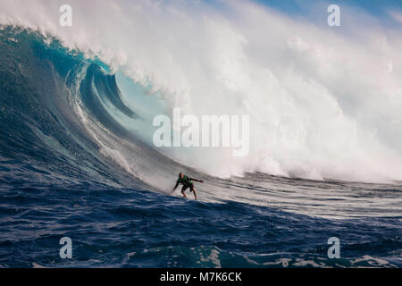 A tow-in surfer drops down the face of Hawaii's big surf at Peahi (Jaws) off Maui.