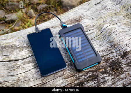 Smartphone charging with pink power bank with solar battery on wood background, selective focus and soft focus - Stock Photo