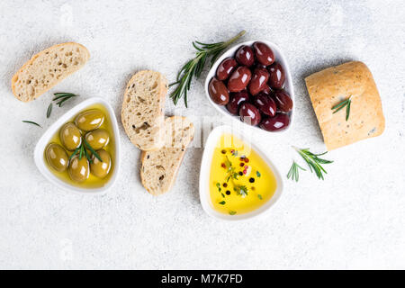 Mediterranean snacks. Ciabatta bread, olives, oil, herbs and spices on white background. Top view - Stock Photo