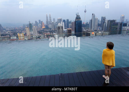 Young boy standing by a luxury infinity swimming pool wrapped in a yellow towel and admiring the scenic night view - Stock Photo