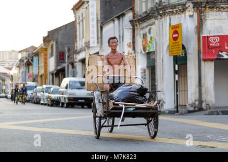 Rikshaw driver on a street in town centre and traditional Chinese shop houses in the UNESCO World Heritage zone - Stock Photo