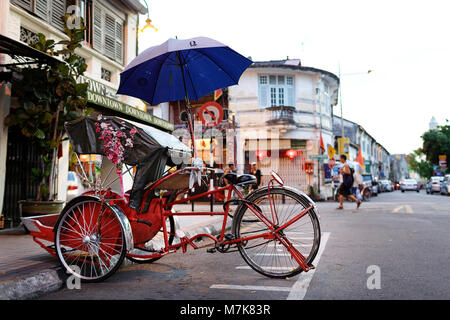 Rikshaw and traditional Chinese shop houses in the UNESCO World Heritage zone of Georgetown in Penang, Malaysia - Stock Photo