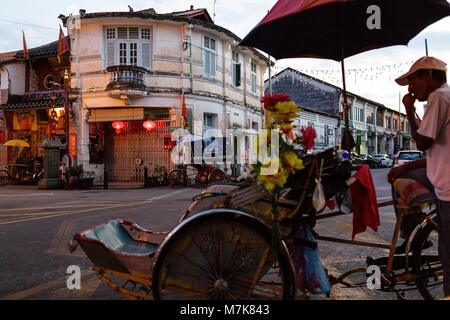 Rikshaw driver and traditional Chinese shop houses on a typical street corner in the UNESCO World Heritage zone - Stock Photo