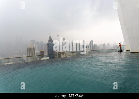 Kuala Lumpur skyline on a rainy day with a luxury swimming pool in the foreground and woman enjoy in the view - Stock Photo