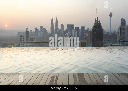 Kuala Lumpur skyline at sunrise with a luxury swimming pool in the foreground - Stock Photo