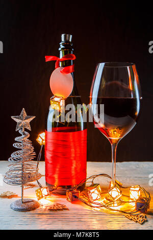 New Year's photo of bottle with red ribbon, Christmas tree toys, wine glass - Stock Photo