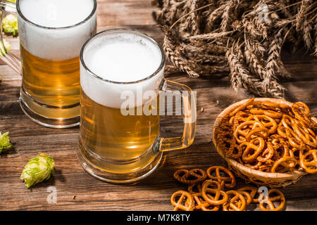 Mugs frothy beer, hops, pretzels and wheat on wooden table - Stock Photo