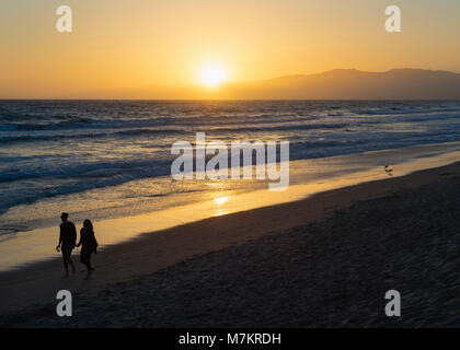 A couple walking down the beach holding wine glasses in Venice Beach, Los Angeles, California. - Stock Photo