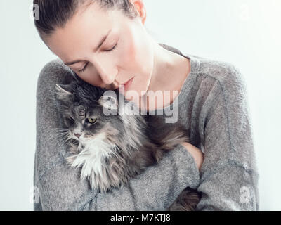 Stylish, young woman gently hugging her kitten on a white background. People, pets, care - Stock Photo