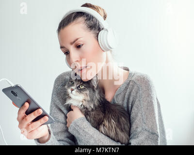 Stylish, young woman in headphones and with mobile phone, gently hugging her kitten on a white background. People, - Stock Photo