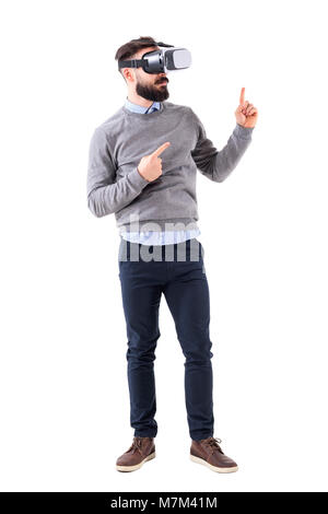 Smart casual businessman wearing vr glasses pointing finger up at copyspace. Full body isolated on white background. - Stock Photo