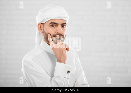 Young attractive muslim male in traditional Islamic cloting thinking about something - Stock Photo