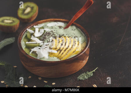 Green kale vegan smoothie bowl with coconut, chia, apple and kiwi. Healthy vegan food concept. Dark rusty background, - Stock Photo