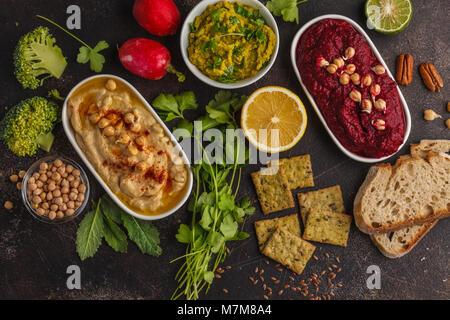 Vegan food background. Vegetarian snacks: hummus, beetroot hummus, green peas dip, vegetables, tofu. Top view, dark - Stock Photo