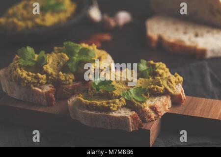 Green peas hummus sandwiches on a dark background. Healthy vegan food concept. - Stock Photo