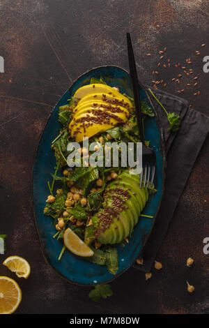 Healthy vegan avocado, chickpeas, kale salad in a vintage blue plate on a dark rusty background. Vegan food concept. - Stock Photo
