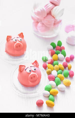 Sweet delicate macaroons of pink marzipan in the form of a mini-pig marshmallows, peanuts in sugar pastel colours - Stock Photo