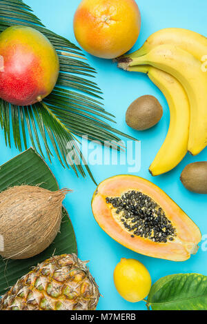 Ripe Juicy Mango Halved Papaya Coconut Kiwi Bananas on Large Palm Leaf on Blue Background. Summer Vacation Relaxation - Stock Photo