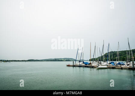 Mattsee, Austria - August 6, 2017: Sailing boats moored in Mattsee Lake a rainy day - Stock Photo